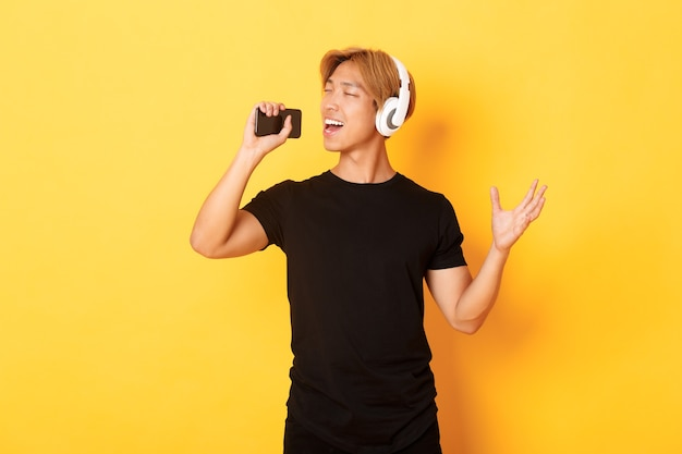 Joyful attractive korean guy in headphones, playing karaoke app, singing into mobile phone microphone, standing yellow wall