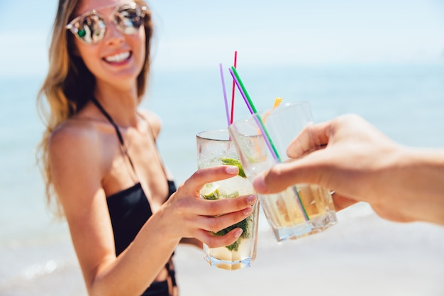 Joyful attractive woman in sunglasses drinking a cocktail with friend, toasting