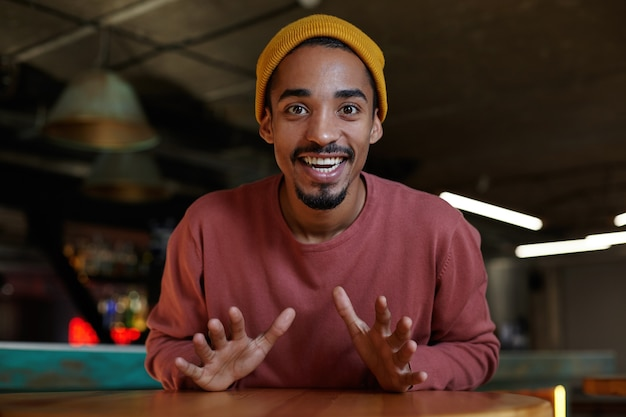 Joyful attractive young bearded dark skinned man looking happily and demonstrating his white perfect teeth, wearing casual clothes over cafe interior