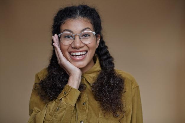 幸せな広い笑顔で見ながら、立っている間彼女のあごに手のひらを保持しながら眼鏡をかけている暗い肌を持つうれしそうな魅力的な若い巻き毛のブルネットの女性