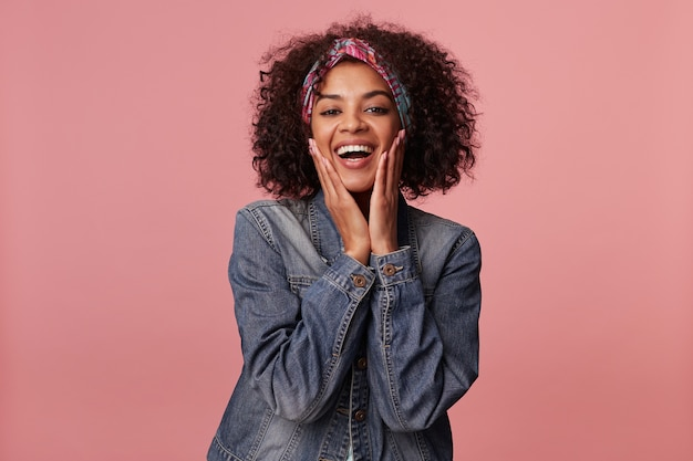 Joyful attractive young curly brunette woman with dark skin wearing casual hairstyle, having colorful headband on her head and holding face with raised palms, isolated