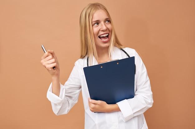 Gioioso attraente giovane dottoressa in camice chirurgico bianco esclamando felicemente con la bocca spalancata, celebrando il successo mentre si lavora in ospedale, rallegrandosi per i buoni risultati delle analisi del sangue