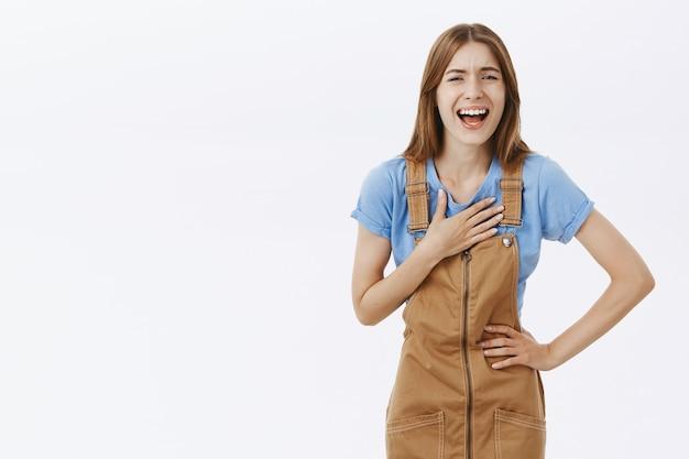 Gioiosa ragazza attraente ridendo e divertendosi, sfondo bianco