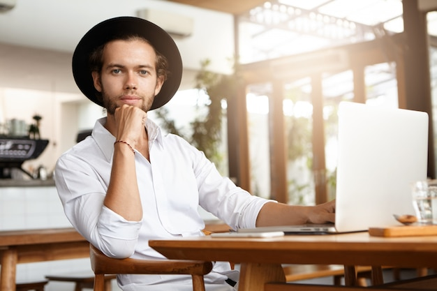 Joyful attractive young student wearing trendy black hat enjoying free wireless connection, browsing internet, using his laptop computer at cafe