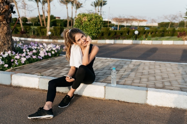 晴れた朝に外でリラックスできるスポーツウェアでうれしそうな魅力的な若い女性。笑顔、熱帯都市、夏の時間、トレーニング、フィットネス、トレーニング。