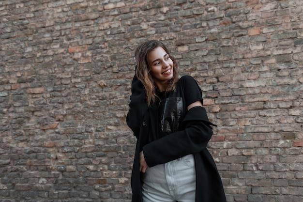 검은 착실히 보내다 세련된 코트에 귀여운 미소로 즐거운 매력적인 젊은 여자