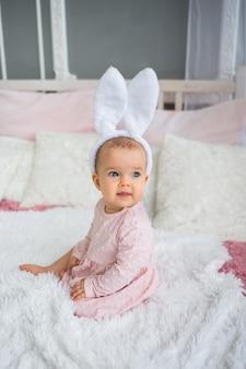Радостная девочка в розовом платье и повязке с заячьими ушками сидит на кровати в комнате