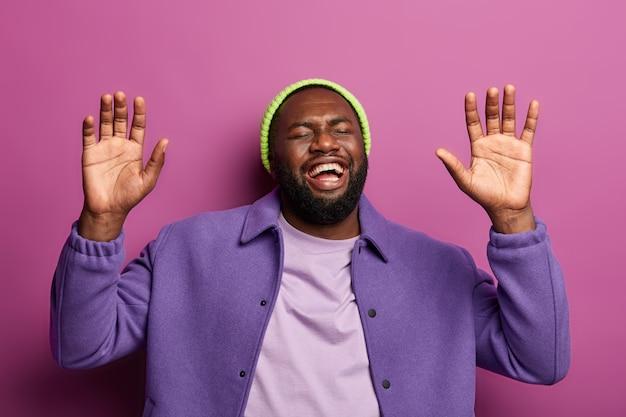 うれしそうなあごひげを生やしたアフリカ系アメリカ人の男は、手のひらを上げ、笑いを止めることができず、面白い逸話を聞き、感情的になりすぎて、陽気なコメディやジョークを見ます