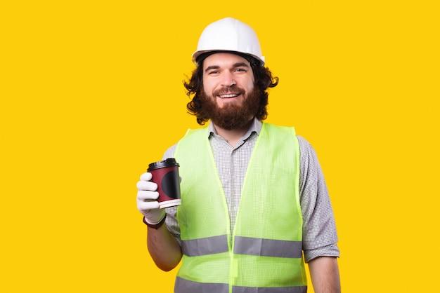 Радостный бородатый архитектор мужчина пьет чашку кофе с собой