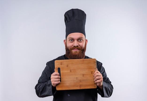Un gioioso chef barbuto uomo in uniforme nera che mostra il bordo della cucina in legno mentre guarda su un muro bianco