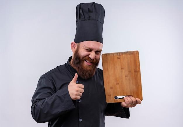 Un uomo barbuto gioioso dello chef in uniforme nera che mostra il bordo della cucina in legno con i pollici in su su un muro bianco