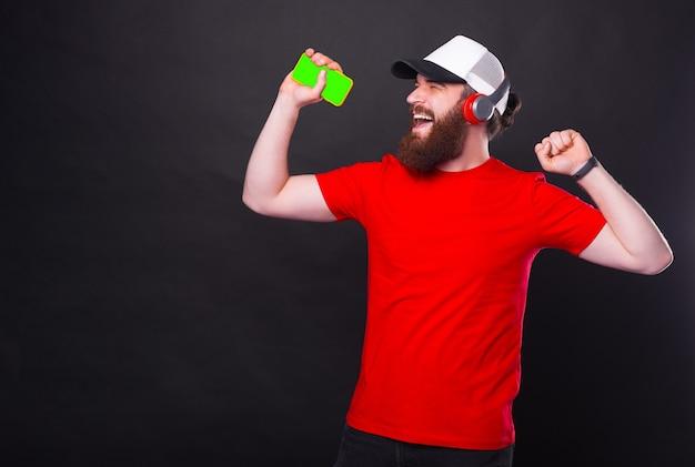 무선 헤드폰에서 빨간색 티셔츠 듣는 음악에 즐거운 수염 된 hipster 남자