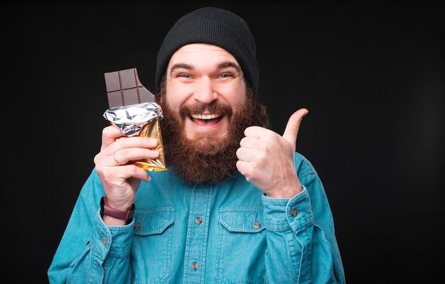Радостный бородатый хипстер показывает палец вверх и держит плитку темного шоколада