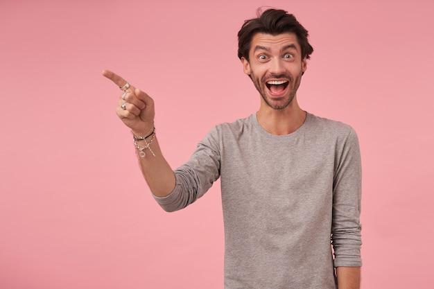 Радостный бородатый мужчина с модной стрижкой стоит, в повседневной одежде, удивленно смотрит и поднимает брови, указывая в сторону указательным пальцем