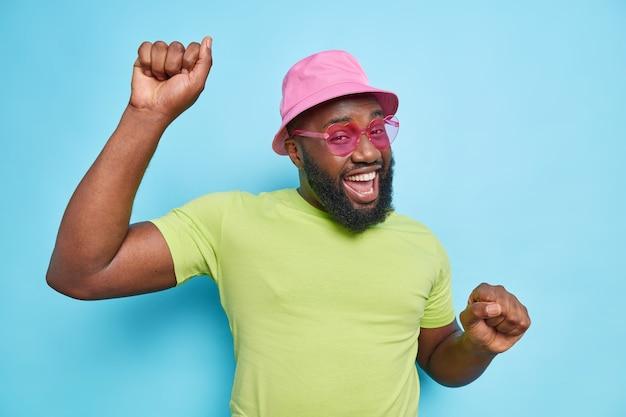 수염을 기른 즐거운 남자가 팔짱을 끼고 평온하게 춤을 추며 행복한 미소를 지으며 행복하게 분홍색 파나마 캐주얼 녹색 티셔츠 선글라스를 착용하고 파란 벽 위에 검은 피부가 고립되어 있습니다