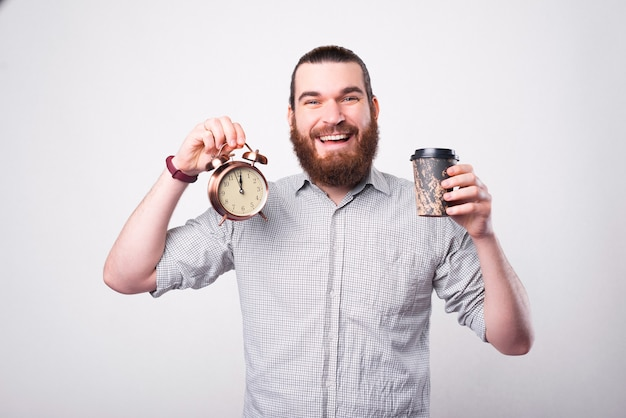 A joyful bearded man is holding his coffee and a little clock and smiling is looking at the camera near a white wall