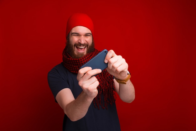 Joyful bearded man is playing in his smartphone near red background.