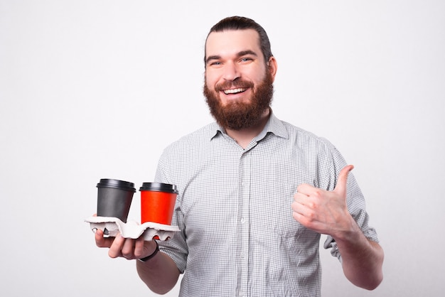 Joyful bearded man is smiling at the camera showing a thumb up because he likes the hot drink that he is holding in the papper cups near a white wall
