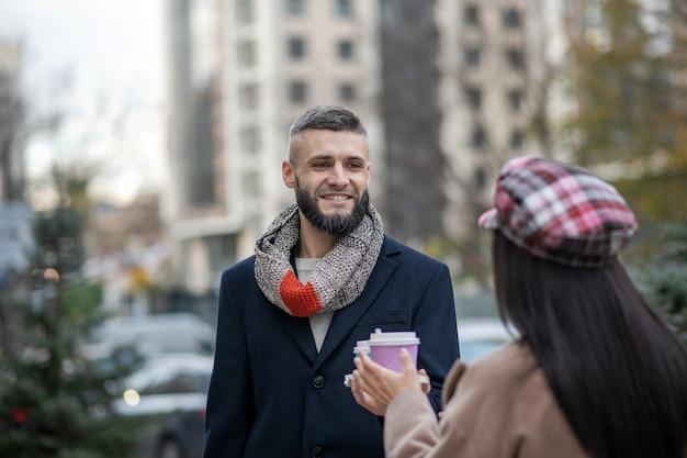 Радостный бородатый мужчина стоит со своей девушкой, когда ему предлагают чашку кофе