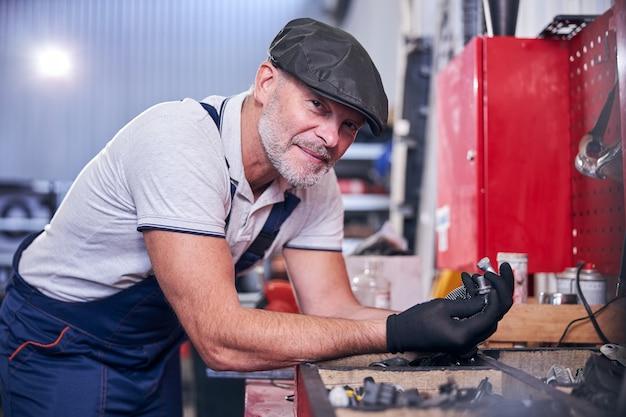 Радостный бородатый механик в кепке держит серебряные болты