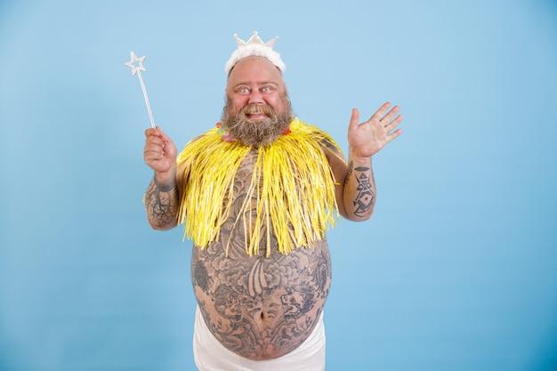Радостный бородатый пухлый мужчина с короной волшебной палкой и желтой накидкой на голубом фоне