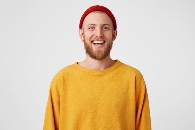 うれしそうなひげを生やした若いかわいい男は、面白い冗談を聞いて、赤い帽子とセーターを着て、楽しく笑います