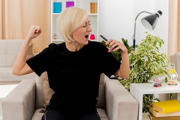 Joyful beautiful blonde russian woman sits on armchair keeping fist and holding phone pretending to sing inside living room