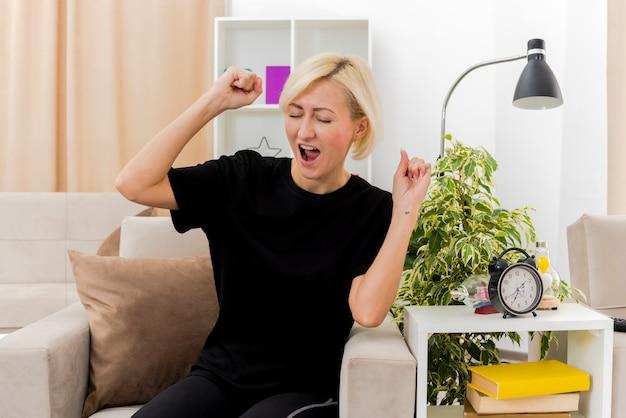 うれしそうな美しい金髪のロシアの女性は、リビングルームの中で拳を上げて肘掛け椅子に座っています