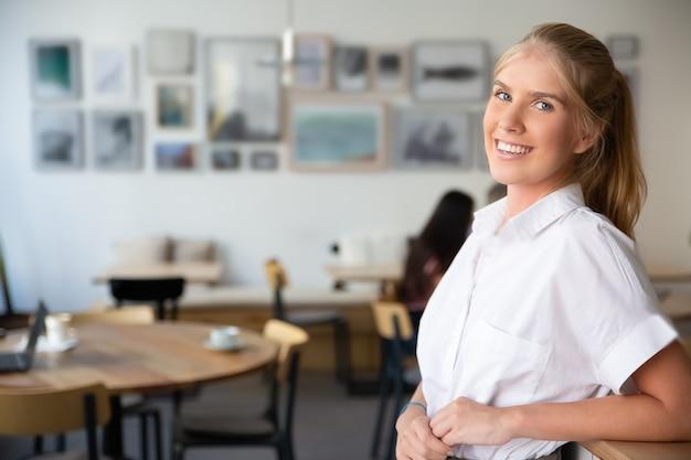 Gioiosa bella donna bionda che indossa una camicia bianca, in piedi in uno spazio di co-working, appoggiato sulla scrivania, in posa,