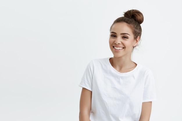 Радостная красивая кавказская женщина с булочкой в прическе носит футболку, выражая радость и хорошее настроение