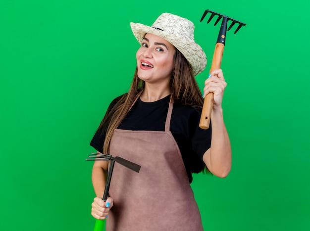 Радостная красивая девушка-садовник в униформе в садовой шляпе держит грабли для мотыги и поднимает грабли, изолированные на зеленом