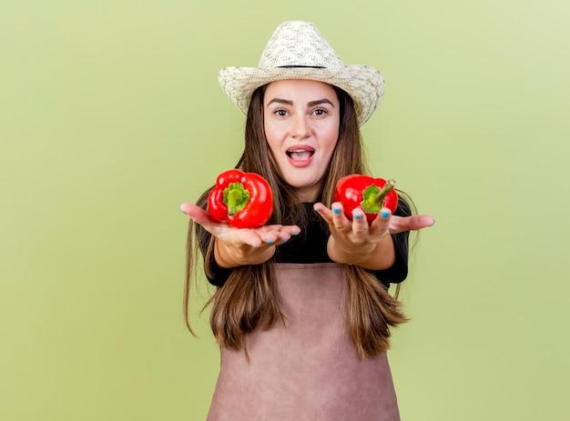 オリーブグリーンの背景に分離されたカメラで唐辛子を差し出す園芸帽子をかぶって制服を着たうれしそうな美しい庭師の女の子
