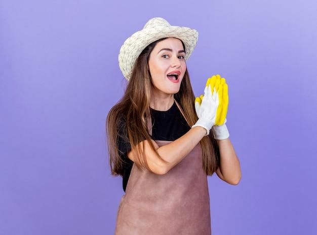 Gioiosa bella ragazza giardiniere in uniforme che indossa cappello da giardinaggio e guanti che mostrano pregare gesto isolato sul blu