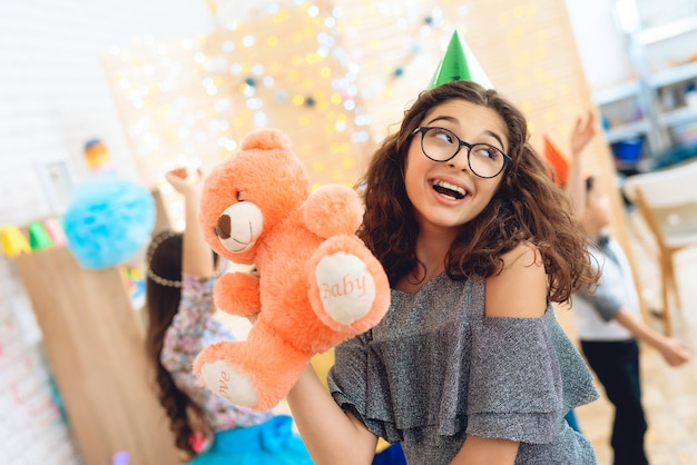 Joyful beautiful girl in green festive hat is pleased with teddy bear on birthday holiday.