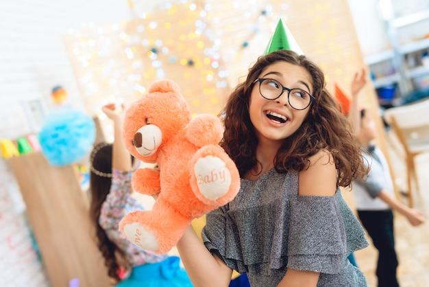 Радостная красивая девушка в зеленой праздничной шапке довольна плюшевым мишкой на день рождения.