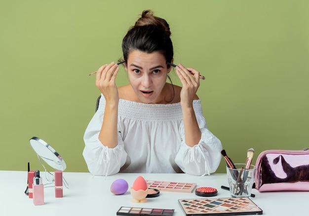 うれしそうな美しい少女が化粧道具でテーブルに座って緑の壁に隔離された寺院に化粧ブラシを置きます
