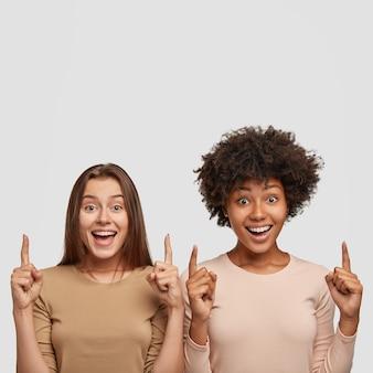 Le belle donne gioiose di razza mista hanno espressioni soddisfatte, puntano verso l'alto