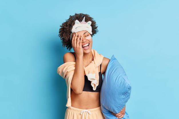 うれしそうな美しい女性の巻き毛は手のひらで顔を覆い、ナイトウェアに身を包んだ非常に幸せを感じます青い壁に隔離された腕の下に枕を保持