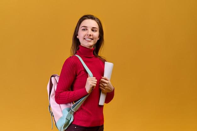 Радостная красивая молодая женщина, одетая в повседневную одежду, смотрится позитивно в сторону