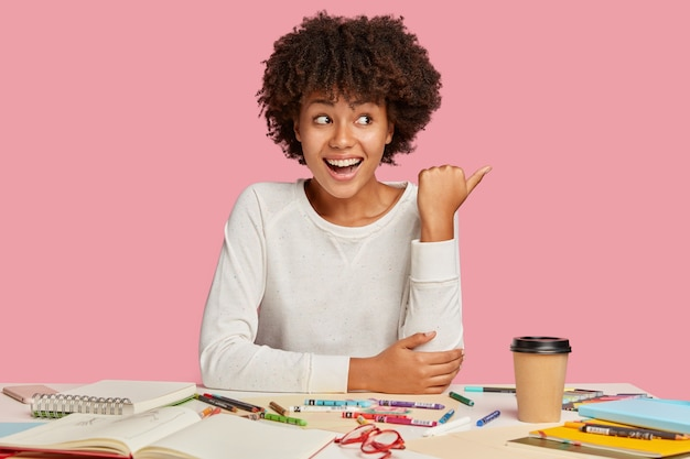 Joyful black creative lady has positive expression, points aside with thumb, shows free space for advertisement, poses at workplace with spiral notebook and crayons, isolated over pink wall
