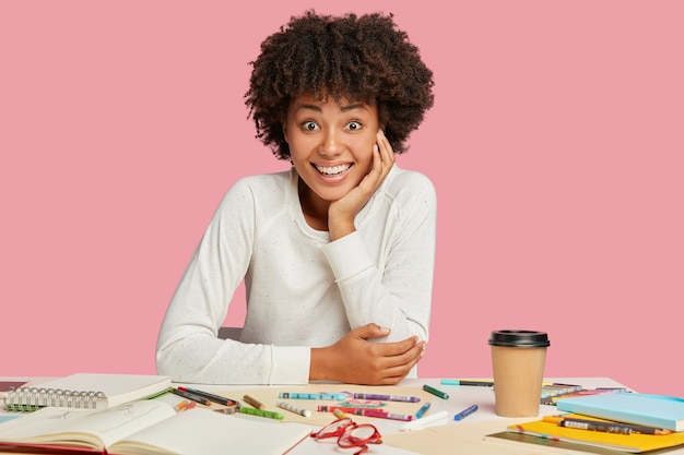 Joyful black designer thinks on idea for sketch, has toothy smile