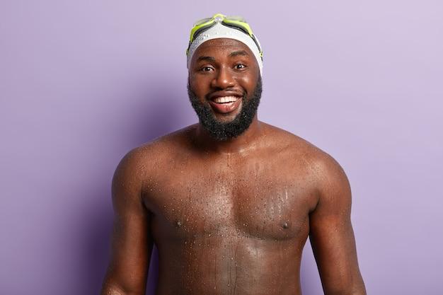 즐거운 흑인 남자는 강한 몸매를 가지고 있으며 젖은 몸통을 보여주고 레크리에이션 시간과 수영을 즐깁니다.