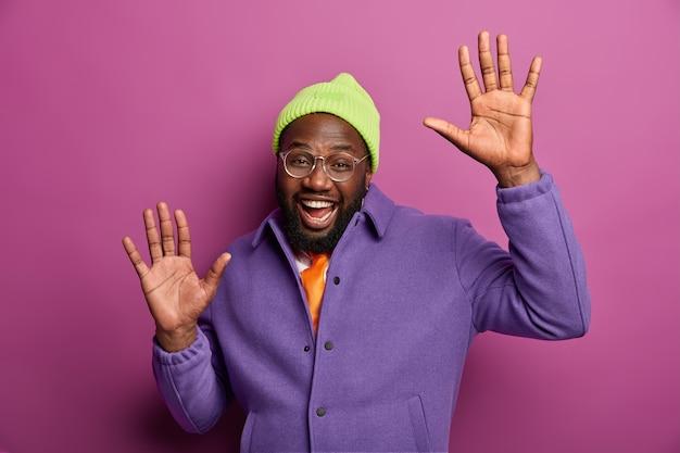즐거운 흑인 남자는 행복으로 손바닥을 들고, 행복하게 춤을 추고, 파티를 즐기고, 평온함을 느끼고, 성공적인 라이프 스타일을 즐기고, 녹색 세련된 모자를 쓰고 있습니다.