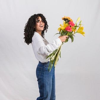 Joyful black woman holding flowers bouquet