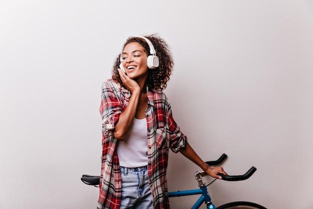 즐거운 흑인 여성이 음악을 듣고 자전거와 함께 포즈. 화이트에 웃 고 셔츠 물결 모양의 머리를 가진 매력적인 아가씨의 실내 샷