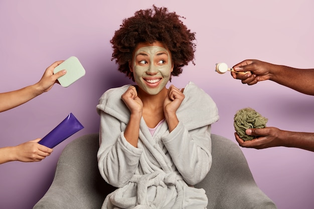 Joyful black woman relaxes with clay facial mask, undergoes skincare procedure