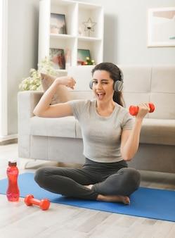 Gioiosa sbatté le palpebre facendo un gesto forte ragazza che indossa le cuffie che si esercita con il manubrio sul tappetino da yoga davanti al divano nel soggiorno