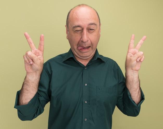올리브 녹색 벽에 고립 된 평화 제스처와 혀를 보여주는 녹색 티셔츠를 입고 즐거운 깜박이 중년 남자