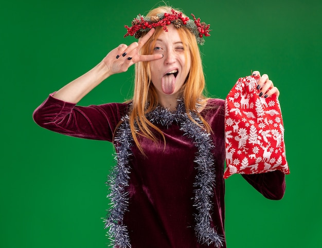 首に花輪と花輪と赤いドレスを着て、舌を示すクリスマスバッグを保持し、緑の背景で隔離の平和ジェスチャーをしているうれしそうなまばたき若い美しい少女