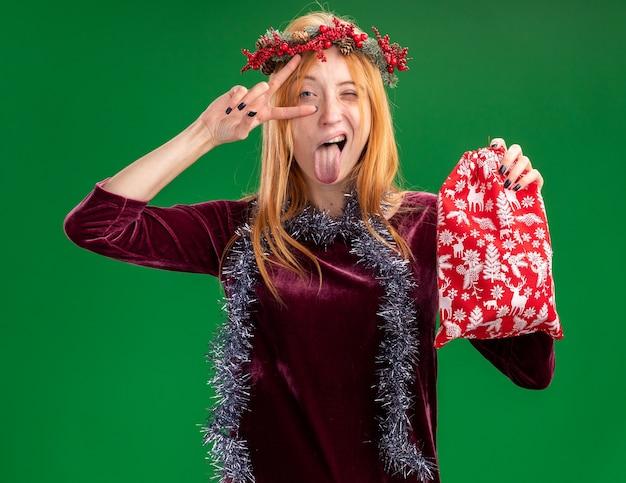 首に花輪と花輪と赤いドレスを着て、舌を示すクリスマスバッグを保持し、緑の壁に隔離された平和ジェスチャーをしているうれしそうなまばたきの若い美しい少女